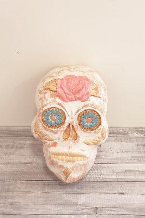 Mascara catrina tallada a mano en madera de cedro. Pintada en blanco envejecido con flores azules en sus ojos, y una rosa en su frente.